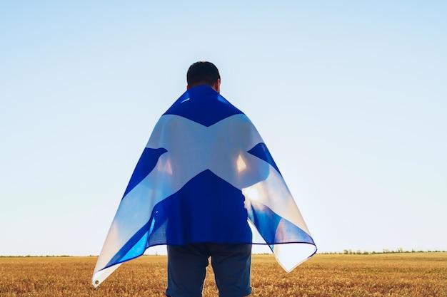 Uomo con una bandiera della scozia in piedi nel campo di mattina