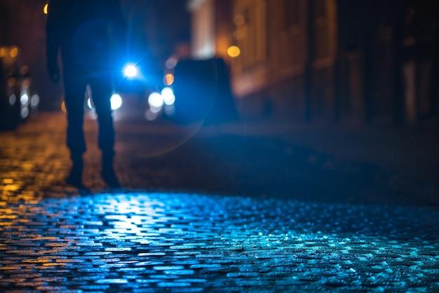 L'uomo con una torcia ispeziona la strada. serata notturna