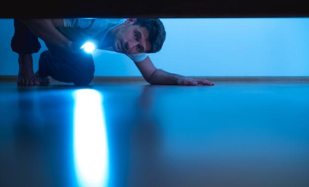 L'uomo con una torcia che guarda sotto il letto. sera notte