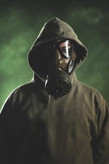 Uomo con maschera antigas su sfondo verde con fumo
