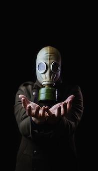 Uomo con la maschera antigas che spande le sue mani su fondo nero