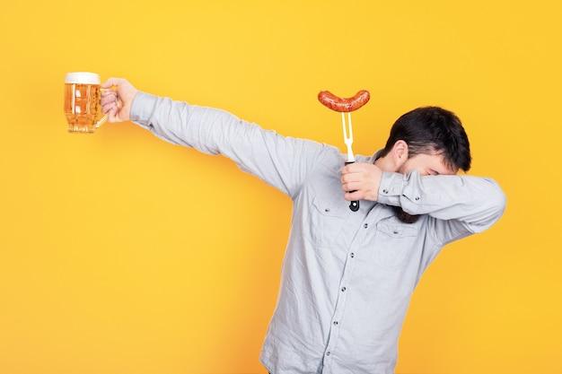Uomo con un bicchiere di birra e salsiccia alla griglia, in piedi nella posa di danza dab