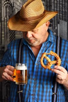 Un uomo con un bicchiere di birra e un pretzel. celebrazione dell'oktoberfest.