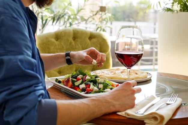 Uomo con bicchiere di vino in una mano nel ristorante.