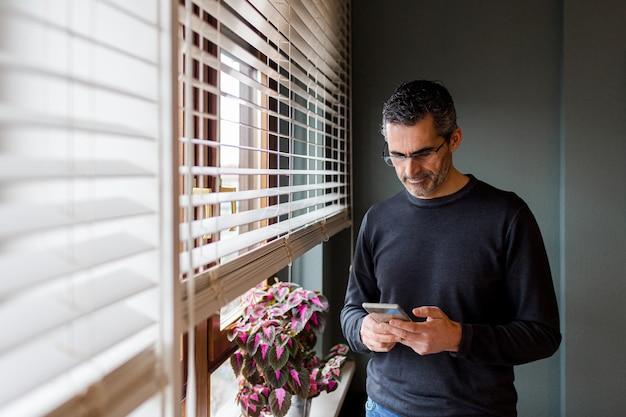 Uomo con occhiali e capelli grigi in chat al telefono dalla finestra di casa sua