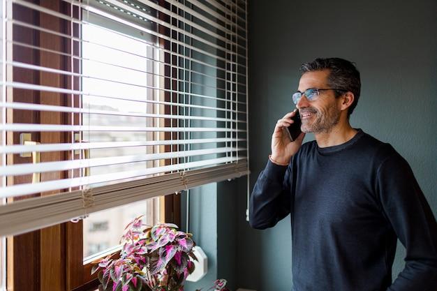 Uomo con occhiali e capelli grigi parla al telefono mentre guarda fuori dalla finestra di casa sua