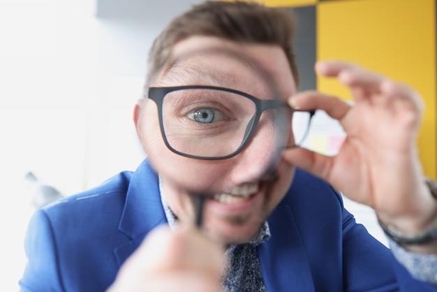 Uomo con gli occhiali che tiene la lente d'ingrandimento davanti all'ispezione finanziaria del primo piano degli occhi financial
