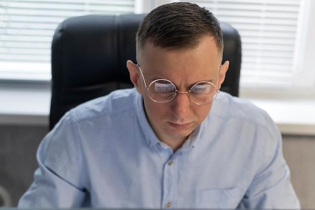 L'uomo con gli occhiali sta lavorando intensamente in ufficio. ritratto del regista in poltrona. il giovane sta lavorando al progetto
