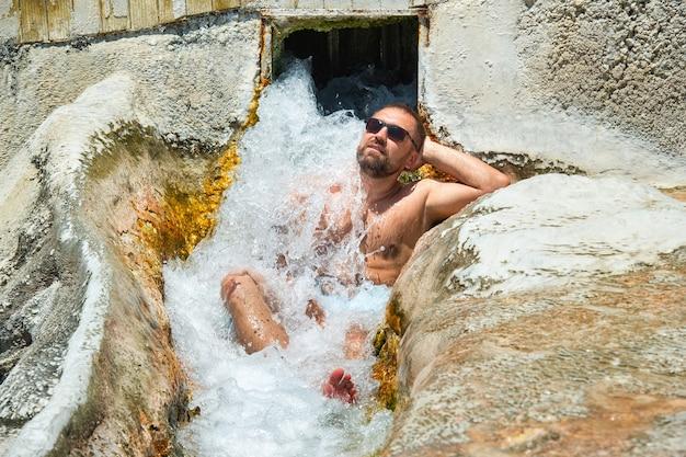 Un uomo con gli occhiali siede sotto una cascata di acqua curativa con sorgenti termali a pamukkale.turchia