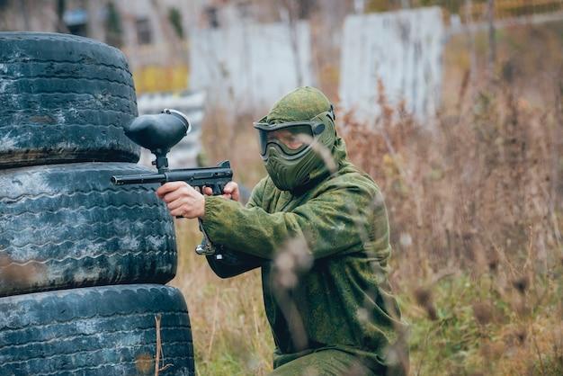 Uomo con la pistola che gioca a paintball. all'aperto