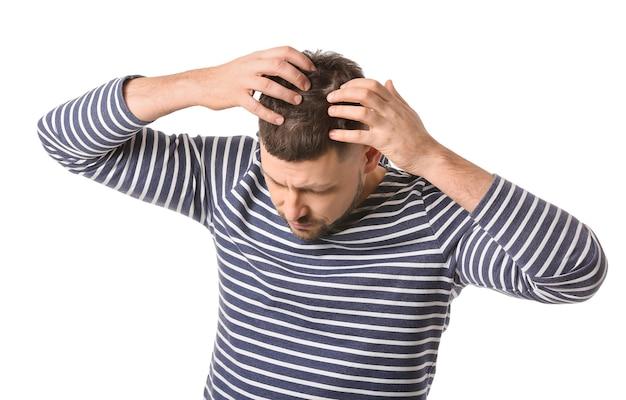 Uomo con problemi di caduta dei capelli sul muro bianco