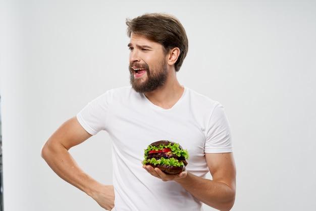 Uomo con hamburger fast food dieta assunzione di cibo maglietta bianca