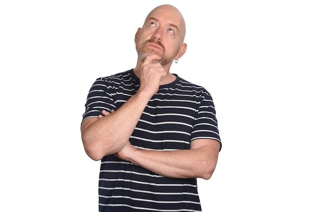 Uomo con la mano sul mento pensando su sfondo bianco