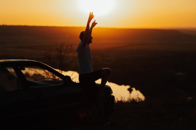 Un uomo con le mani in alto ammira una vista costiera al tramonto. uomo solo in cima alla montagna con il fiume sulla superficie seduto sul cofano dell'auto e godendo il viaggio su strada.