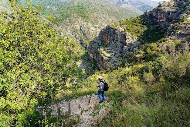 Uomo con cappello che scende lungo il sentiero nel bosco tra le montagne