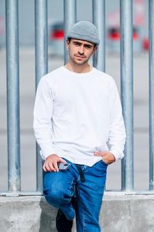 Uomo con cappello, jeans e maglietta bianca in posa sulla strada