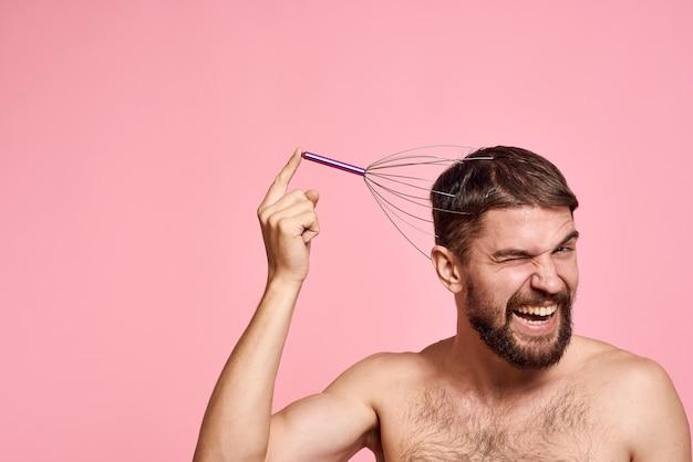 L'uomo con la testa massaggiatore rilassarsi rosa cura del corpo