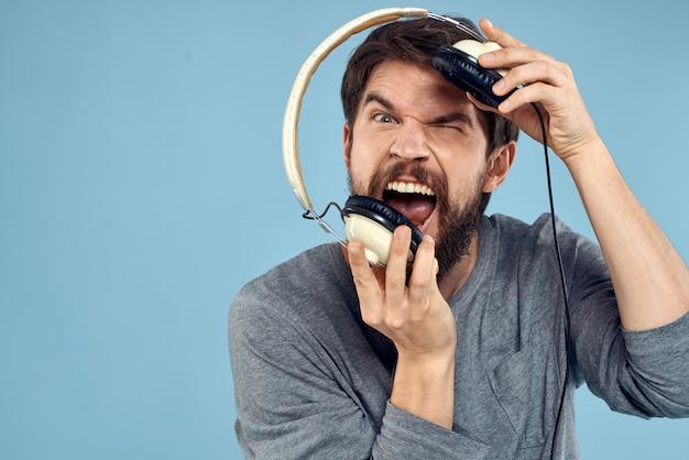 Uomo con le cuffie in mano. concetto di tecnologia di emozione musicale