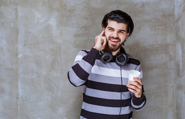 Uomo con le cuffie che tiene una tazza di acqua bianca