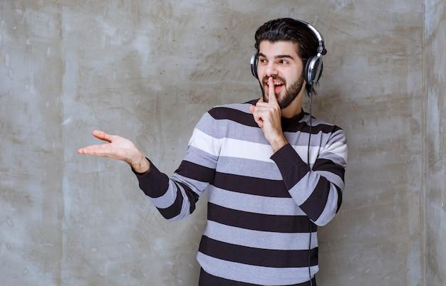 Uomo con le cuffie che ascolta la musica e chiede silenzio Foto Premium