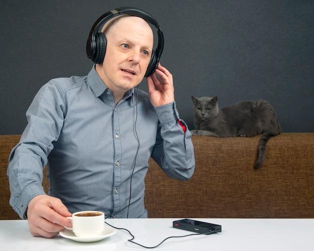 Uomo con le cuffie che ascolta musica e beve un caffè seduto su un divano con un gatto grigio