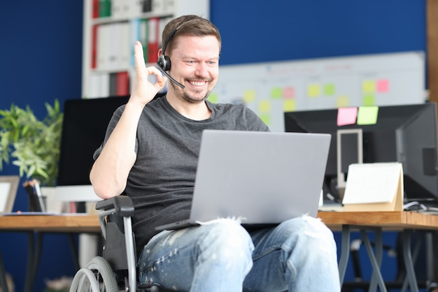 Uomo con cuffie e microfono in sedia a rotelle che mostra il gesto giusto nel computer portatile. freelance per disabili concept