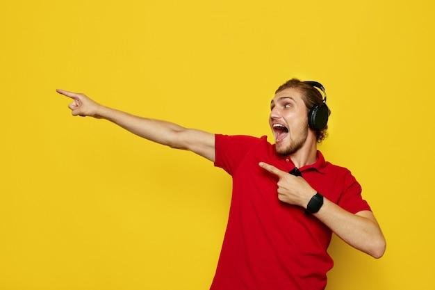 Uomo con le cuffie e la maglietta polo rossa che punta lontano con entrambe le mani