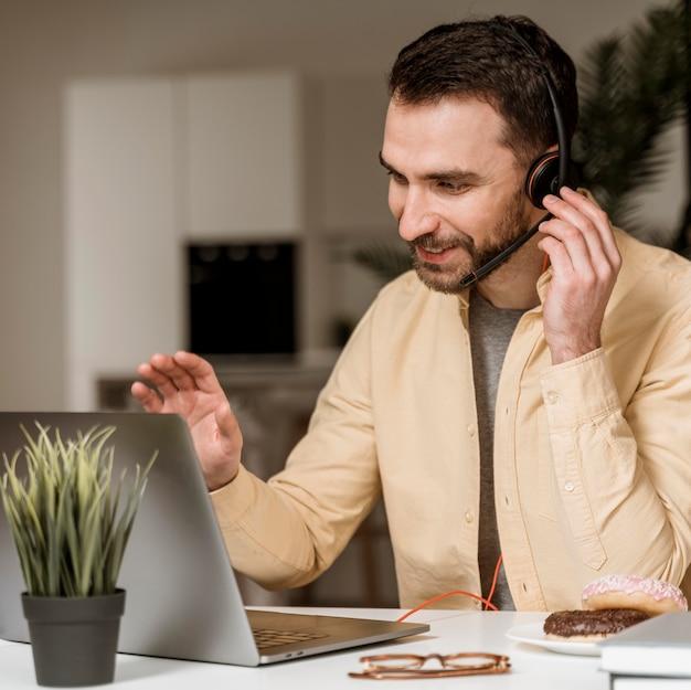 Uomo con auricolare che ha videochiamata sul computer portatile Foto Premium