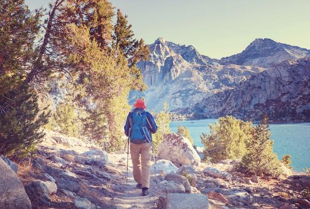 Uomo con attrezzatura da escursionismo a piedi nelle montagne della sierra nevada, in california, usa
