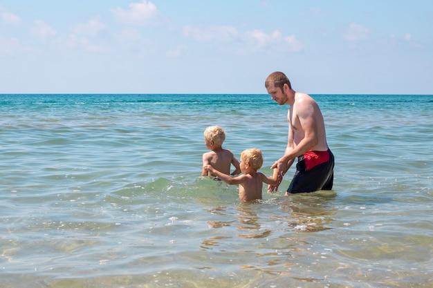 Un uomo con i suoi figli sta nuotando in mare. ragazzi e papà si divertono in acqua.