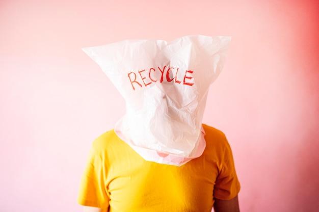 Uomo con la testa coperta da un sacchetto di plastica con la parola riciclare