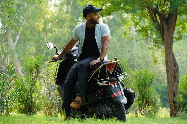 Un uomo con il suo nuovo scooter a grandezza naturale