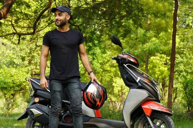 Un uomo con il suo nuovo scooter e casco che rinuncia all'immagine a grandezza naturale