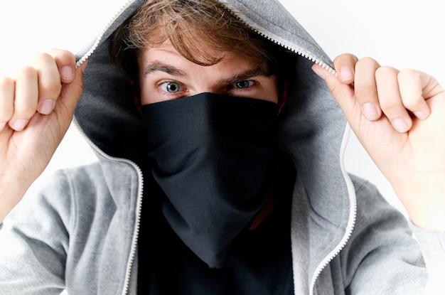 Uomo con un cappuccio sulla sua testa crimine furto studio sfondo chiaro. foto di alta qualità