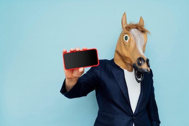 Uomo con maschera di cavallo in tuta in posa isolato su sfondo blu. concetto di stile di vita della gente. mock up copia spazio. tieni il cellulare con lo schermo nero vuoto