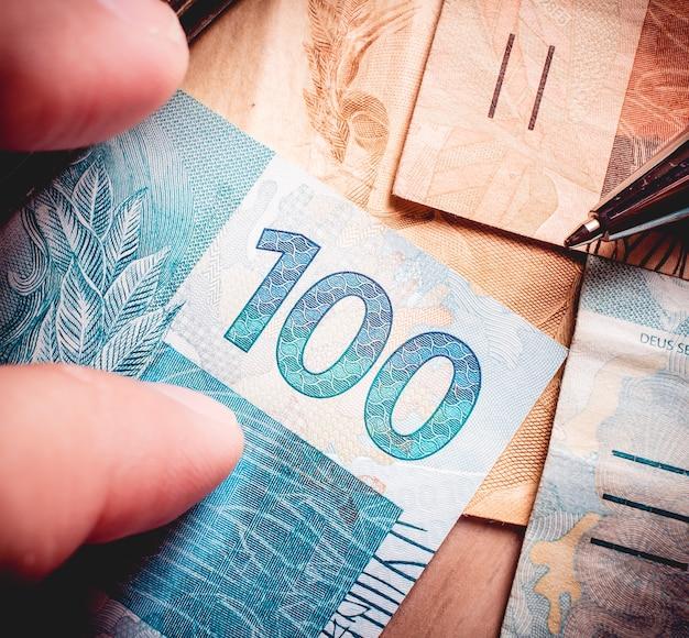 Un uomo con banconote da cento reais del real brasiliano che sono su un mobile di legno
