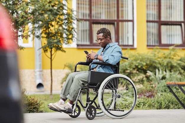 Uomo con gambe malate che legge sms al telefono