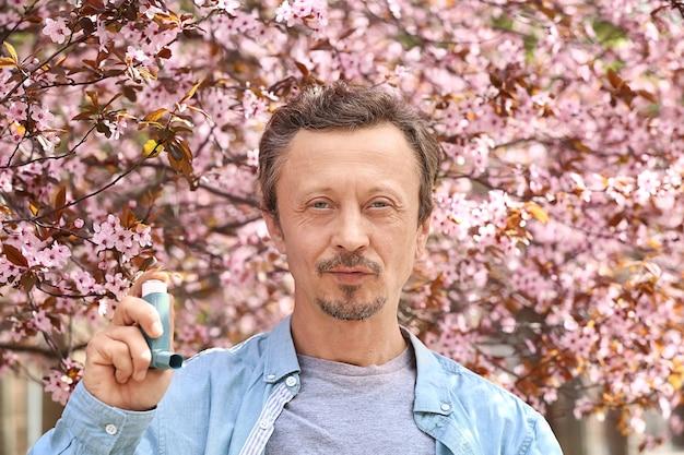 Uomo con inalatore all'aperto il giorno di primavera