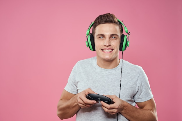 Un uomo con un joystick nelle sue mani cuffie che giocano a giochi intrattenimento lifestyle t-shirt bianca sfondo rosa