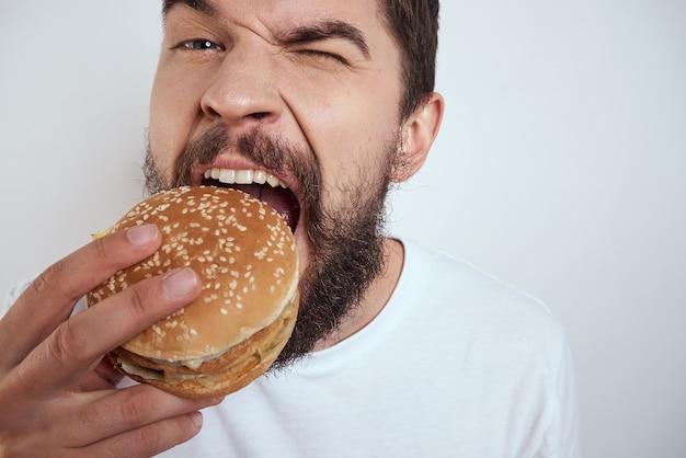 Uomo con cibo spazzatura cibo spazzatura, hamburger e patatine fritte