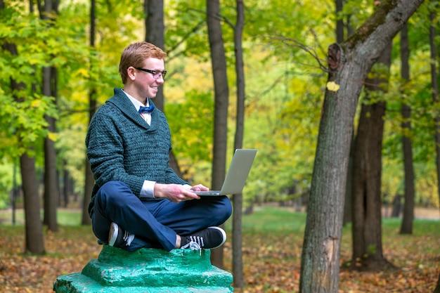 Un uomo con lap top su un piedistallo che finge di essere una statua nel parco in autunno. fatti un'idea