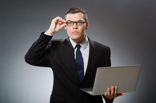 Uomo con il computer portatile nel concetto di affari