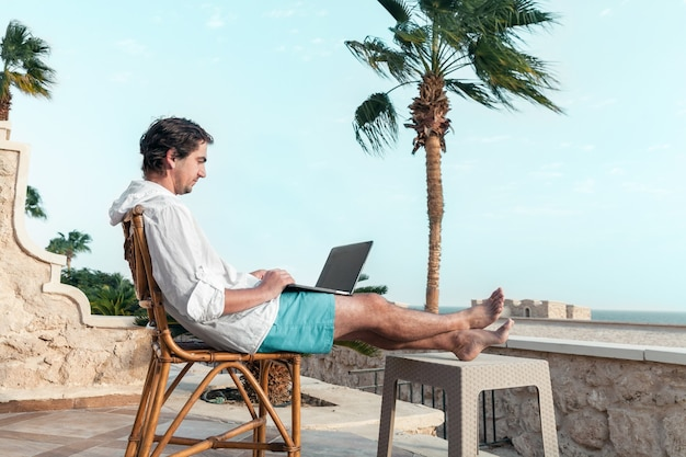 Un uomo con un laptop in mano sta riposando e lavora come libero professionista sul tavolo delle palme