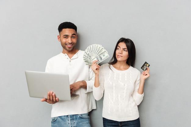 Uomo con il computer portatile che sta donna vicina con la carta e i contanti