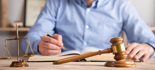 Uomo con libro di legge con giudice e scale sul tavolo