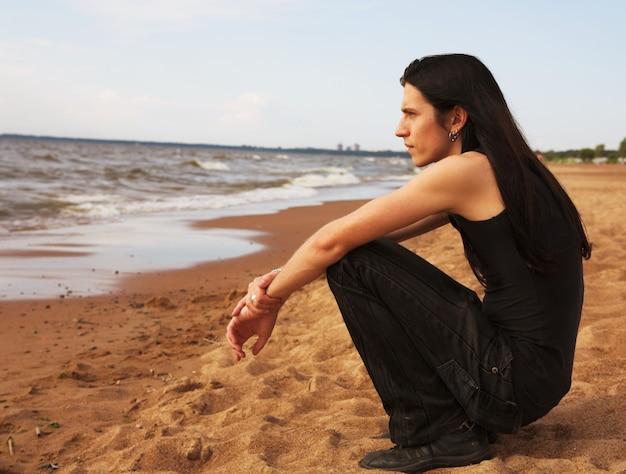 Uomo con i capelli lunghi sulla spiaggia