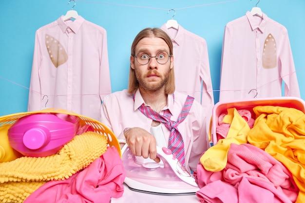 L'uomo con i capelli lunghi stira i vestiti a casa impegnato a fare i lavori domestici indossa occhiali rotondi in piedi vicino a camicie appese alle grucce. faccende di uomini