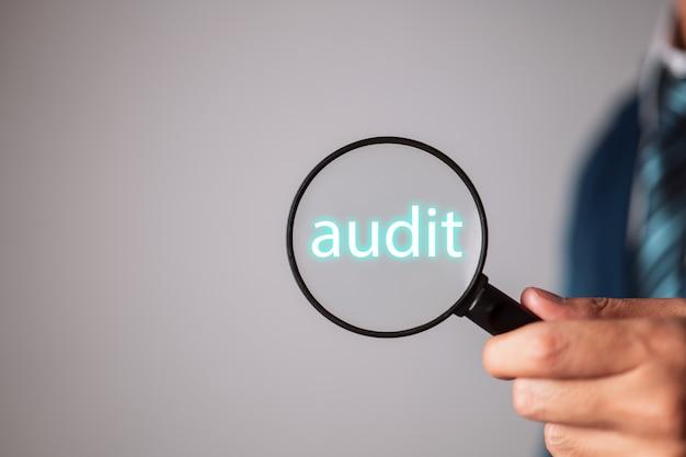 Uomo con una lente d'ingrandimento, il manager dell'uomo d'affari si concentra sull'audit.