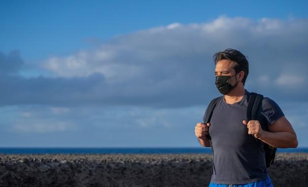 Uomo con maschera e zaino che cammina e guarda verso l'orizzonte nella natura