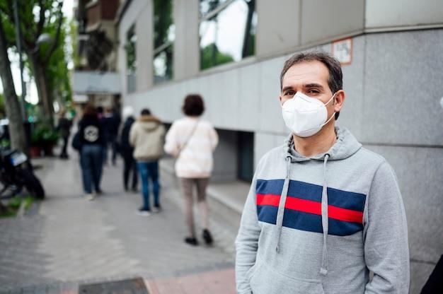 Uomo con la maschera in una fila di persone in attesa